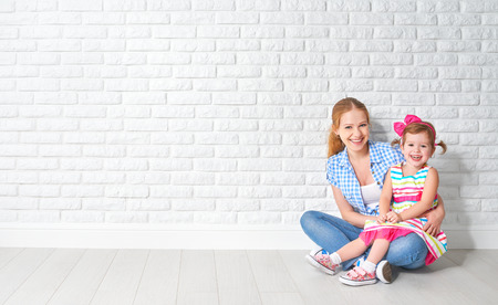 Photo for concept happy family mother and baby daughter, a girl at a blank brick wall of a house move - Royalty Free Image