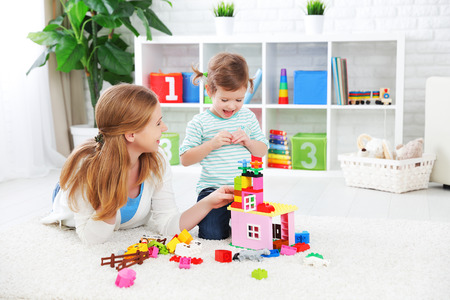Photo for Mother and child daughter playing together, build from the constructor - Royalty Free Image