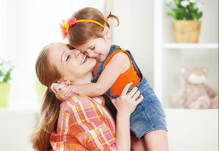 Foto de happy family mother and child girl daughter playing  laughing and hugging at home - Imagen libre de derechos