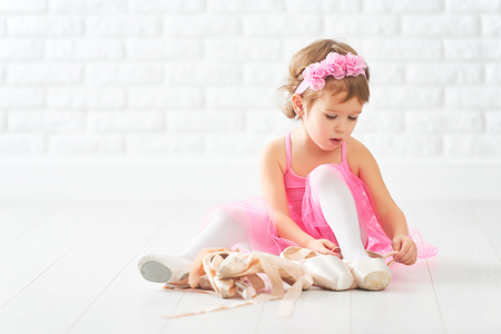 Foto de little child girl dreams of becoming  ballerina with ballet shoes and pointe shoes in a pink tutu skirt - Imagen libre de derechos
