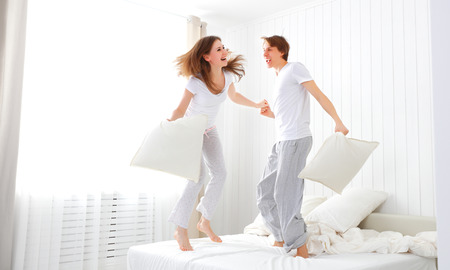 Foto de Happy loving couple jumping and having fun in bed - Imagen libre de derechos