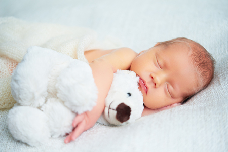 Foto de Cute newborn baby sleeps with a toy teddy bear white - Imagen libre de derechos