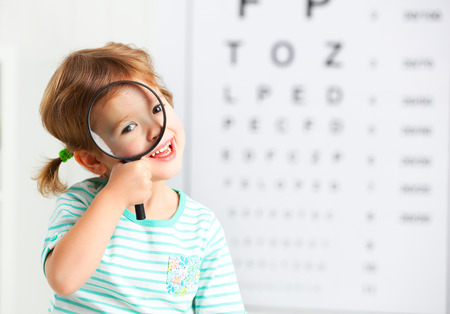 Foto de concept vision testing. child girl with a magnifying glass at the doctor ophthalmologist - Imagen libre de derechos