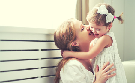 Foto de Happy loving family. mother and child girl playing, kissing and hugging - Imagen libre de derechos