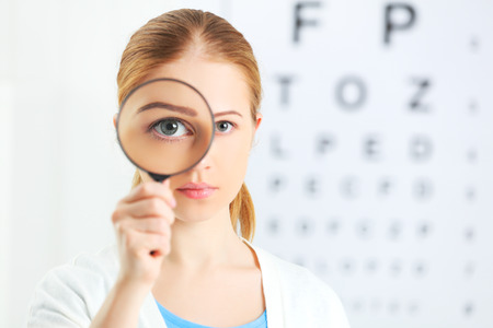 Foto de concept vision testing. woman with a magnifying glass at the doctor ophthalmologist - Imagen libre de derechos