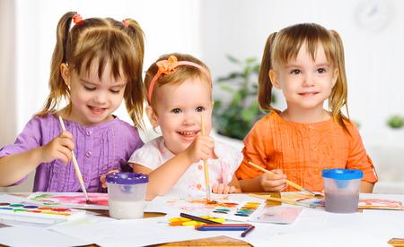 happy sister little girls in kindergarten draw paints