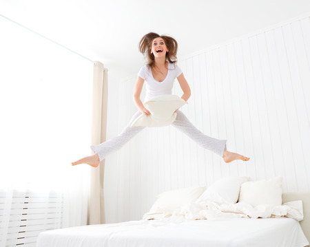 Foto de funny happy girl jumping and having fun in bed - Imagen libre de derechos