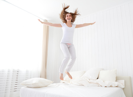 Photo pour funny happy girl jumping and having fun in bed - image libre de droit
