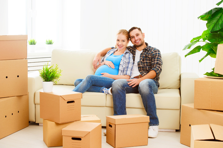 Photo pour moving to a new apartment. young family pregnant wife and husband with cardboard boxes - image libre de droit