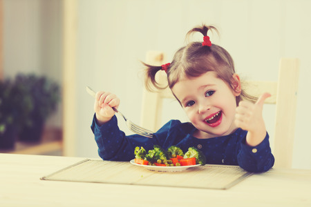 happy child girl loves to eat vegetables and showing thumbs up