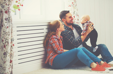 Foto de happy family mother and father playing with a baby at home - Imagen libre de derechos
