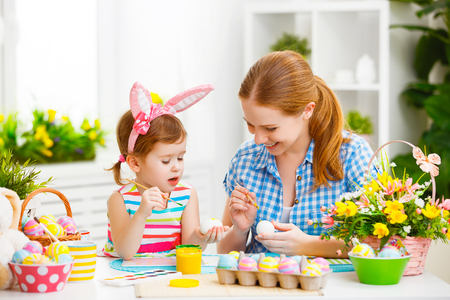 Photo for happy family mother and child girl paints eggs for Easter at home - Royalty Free Image