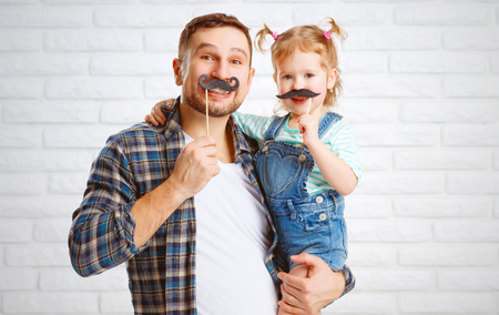 Foto de funny family father and child daughter with a mustache - Imagen libre de derechos