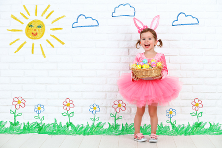 Photo pour concept easter. Happy child girl in a costume bunny rabbit with ears and a basket of eggs - image libre de droit