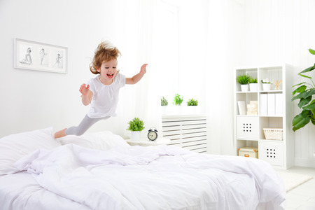 Foto de happy child girl having fun jumps and plays bed - Imagen libre de derechos