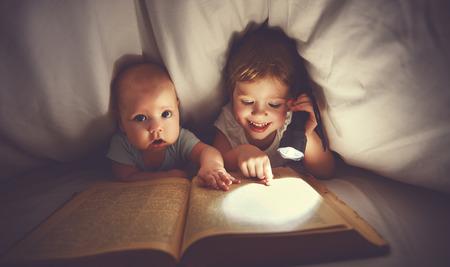 Foto de children brother and sister read a book with aflashlight under blanket in bed - Imagen libre de derechos