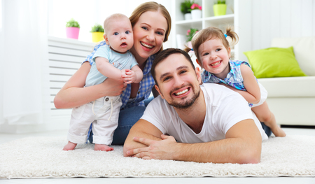 Photo pour happy family mother, father and two children playing and cuddling at home on floor - image libre de droit