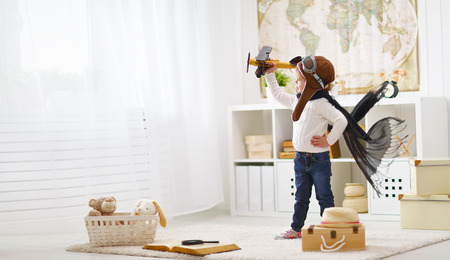 Foto per concept of children's dreams and travels.  pilot aviator child with a toy airplane plays at home in his room - Immagine Royalty Free
