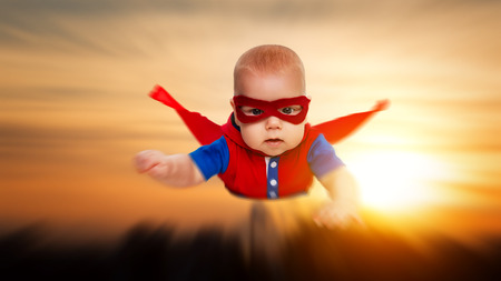 Foto de toddler little baby superman superhero with a red cape flying through the sky - Imagen libre de derechos