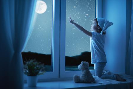 Foto de child little girl at the window dreaming and admiring the starry sky at bedtime night - Imagen libre de derechos