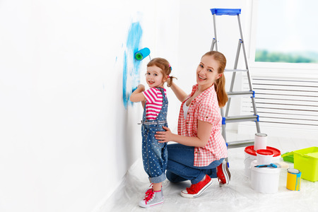 Photo pour happy family mother and child daughter making repairs, paint the wall at home - image libre de droit