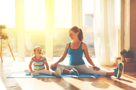 Photo for family mother and child daughter are engaged in fitness, yoga, exercise at home - Royalty Free Image