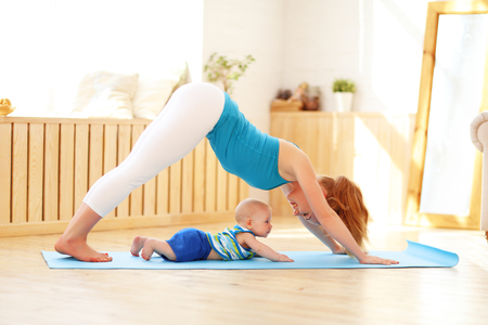 Foto de sports mother is engaged in fitness and yoga with a baby at home - Imagen libre de derechos