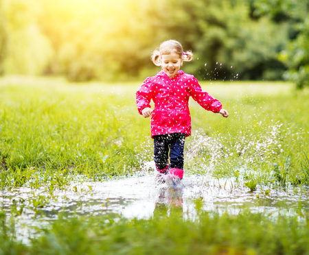 happy child girl running and jumping in puddles after rain in summerの写真素材