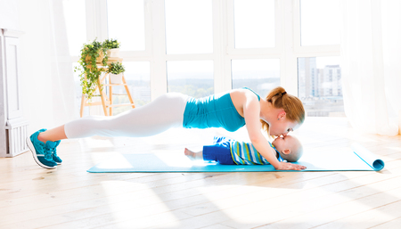 Photo for sports mother is engaged in fitness and yoga with a baby at home - Royalty Free Image
