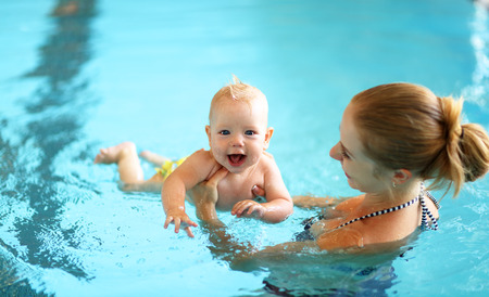 Photo pour healthy family mother teaching baby swimming pool - image libre de droit