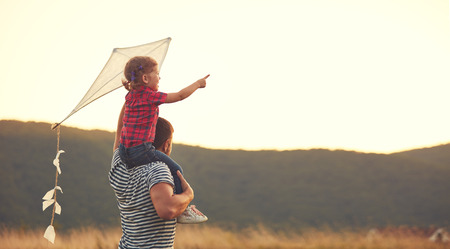 Foto de happy family father and child on meadow with a kite in the summer on the nature - Imagen libre de derechos