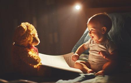 Foto de Happy baby reading a book with teddy bear in bed in the dark - Imagen libre de derechos