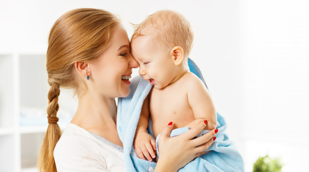 Photo for Happy family mother and baby in a blue towel after bathing in the bath - Royalty Free Image