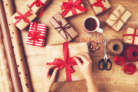 Photo for hand of woman  packs boxes with Christmas gifts presents on a wooden table - Royalty Free Image