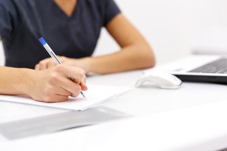 Photo pour hand business woman writing pen on paper next to computer on desktop - image libre de droit