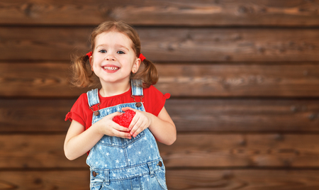 Foto de happy laughing child girl with heart Valentine's Day, wooden background - Imagen libre de derechos