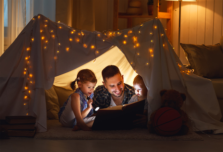 Photo pour happy family father and children reading a book with a flashlight in a tent at home - image libre de droit