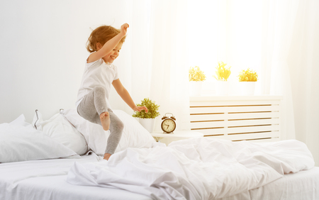 Photo for happy child girl having fun jumps and plays bed - Royalty Free Image