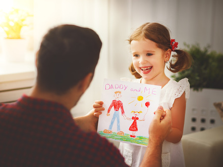 Father's day. Happy family daughter giving dad a greeting card on holidayの写真素材