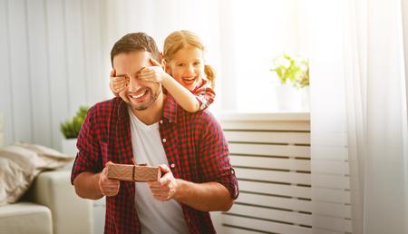 Foto de Father's day. Happy family daughter hugging dad and laughs on holiday - Imagen libre de derechos