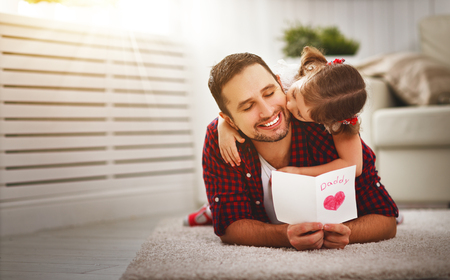 Photo for Father's day. Happy family daughter kiss dad and giving greeting card  on holiday - Royalty Free Image