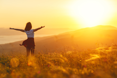 Photo for Happy woman standing with her back on the sunset in nature in summer with open hands - Royalty Free Image