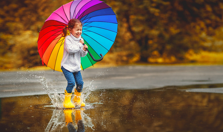 Happy funny ba child by girl with a multicolored umbrella jumping on puddles in rubber boots and laughingの写真素材