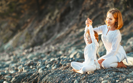 Photo for Happy family mother and child daughter doing yoga, meditate in lotus position on beach at sunset  - Royalty Free Image