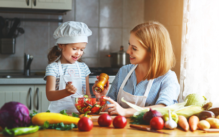 Healthy eating. Happy family mother and child  girl preparing vegetarian vegetable salad at home in kitchenの写真素材