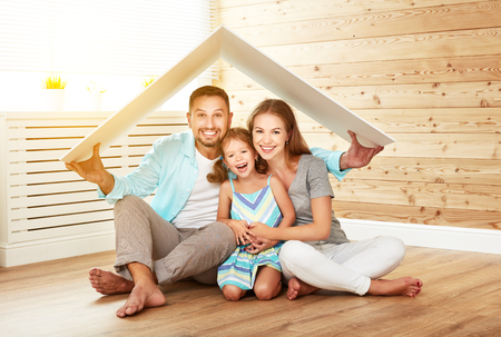Photo for Concept housing a young family. Mother, father and child in new house with a roof - Royalty Free Image