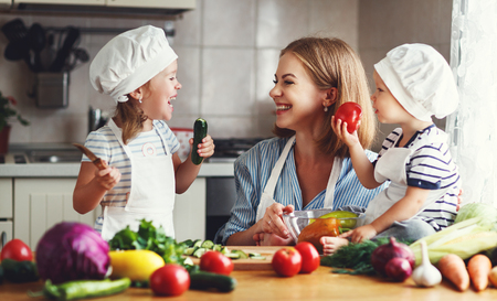 Photo pour Healthy eating. Happy family mother and children  prepares   vegetable salad in kitchen - image libre de droit