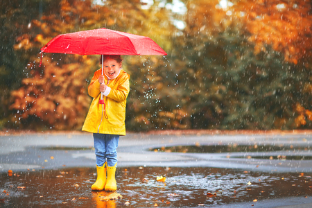 happy child girl with an umbrella and rubber boots in puddle on an autumn walkの写真素材
