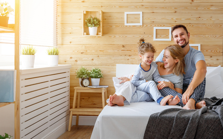 Photo pour happy family mother, father and child daughter laughs in bed - image libre de droit