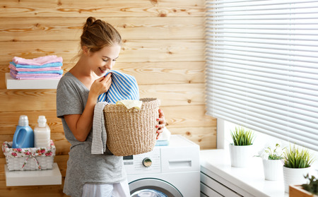 a Happy housewife woman in laundry room with washing machineの写真素材